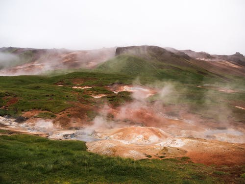 Hilled country with geysers blowing steam off among grass area against volcanic mountains in cloudy day