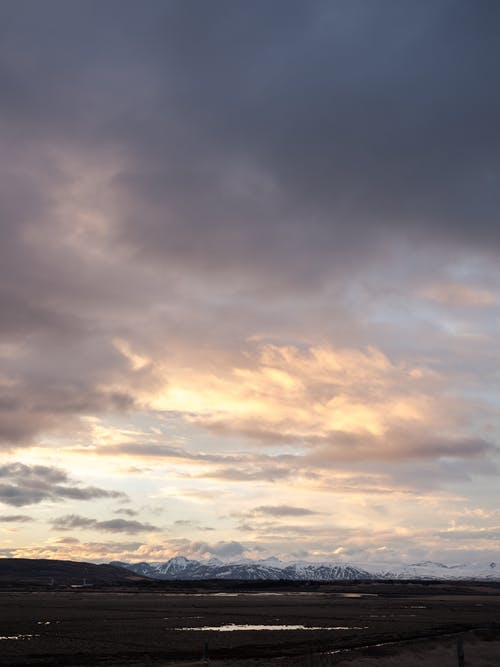 Moving dark clouds in sky at sunset over remote field and hills with snowy mountain ridges