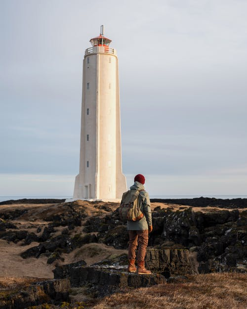 Unrecognizable tourist admiring lighthouse on seashore