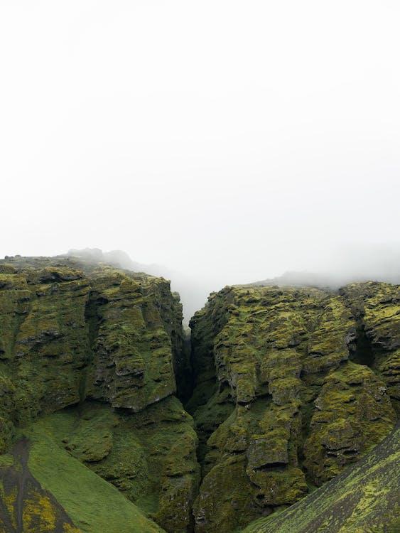 Green rocky slope on misty day