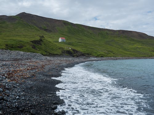 Rocky seashore with rural house near sea