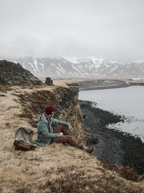 Side view full body of anonymous male tourist in casual warm clothes with backpack resting on stony seashore near calm sea against majestic snowy mountains on overcast day