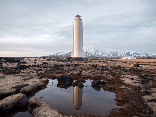 Lighthouse on remote seashore against snowy mountain