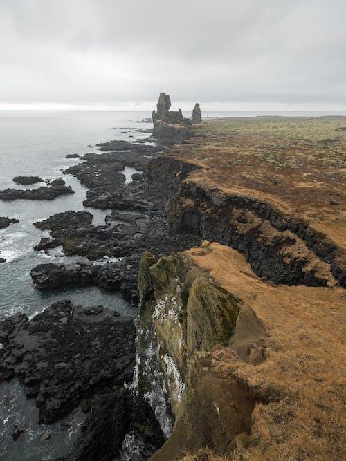Spectacular view of rocky coastline against calm ocean waves under cloudy dark sky