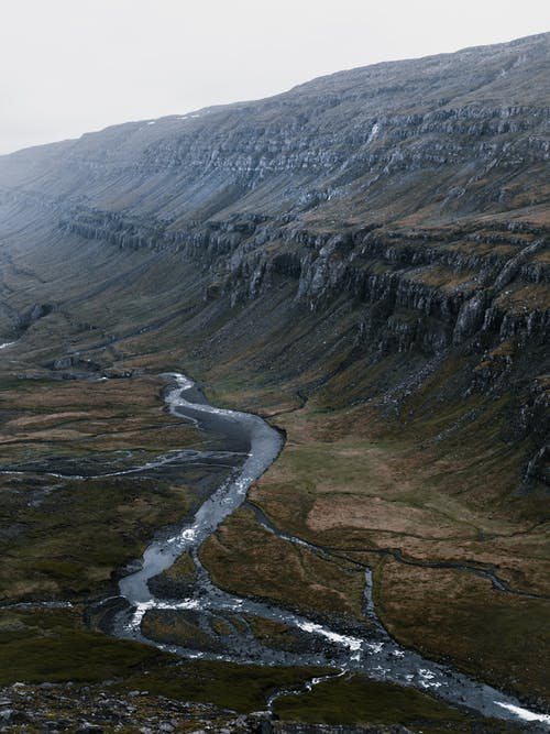Picturesque view of narrow curvy rapid stream flowing through mountainous mossy terrain on cloudy morning