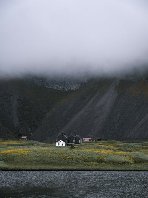 Remote houses on mountain valley under cloudy sky