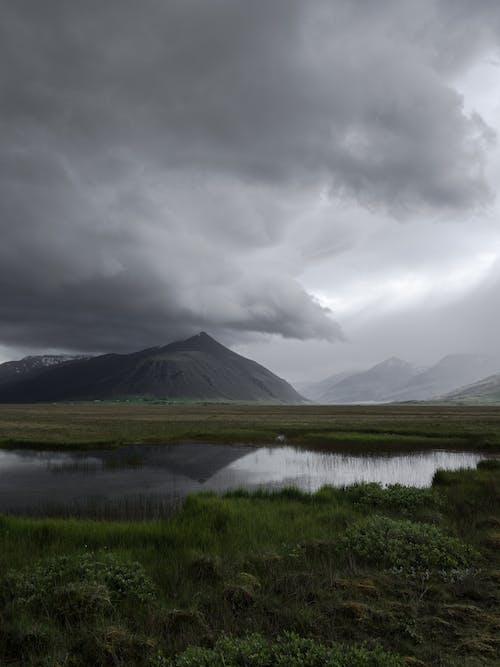 Dark cloudy low sky over mountain lake