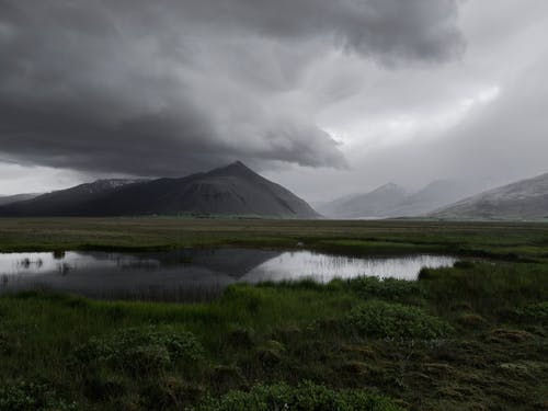 Majestic view of rough mountainous terrain with green valley and cold lake under gloomy dark cloudy sky