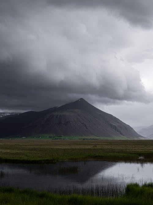 Dark cloudy sky over mountain valley and lake