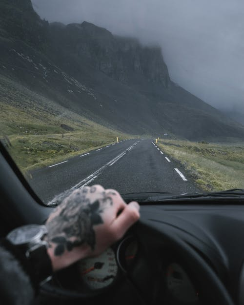 Crop anonymous traveler with tattooed hand on car steering wheel driving along road near mountains on overcast gloomy weather
