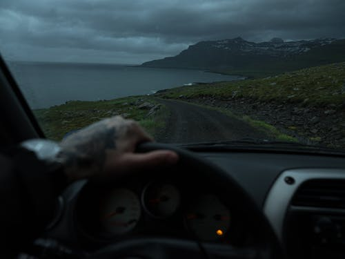 Crop anonymous person with hand on steering wheel driving along narrow rural road towards calm sea and dramatic rocky mountains under cloudy dark sky at night
