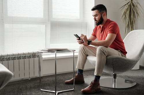 Man in Red Polo Shirt and Beige Pants Sitting on Chair Holding Smartphone