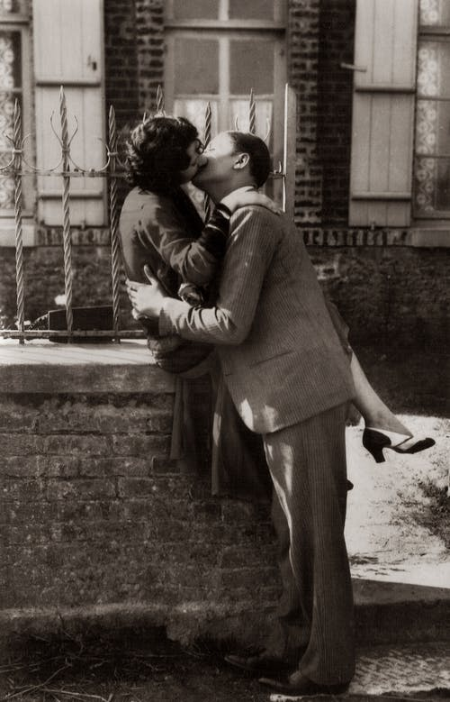 Man and Woman Kissing on Sidewalk