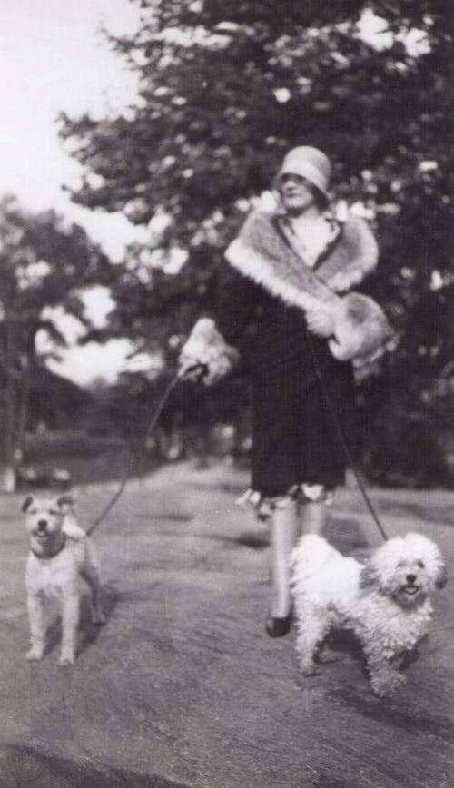 Grayscale Photo of Woman Carrying Dog