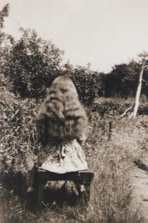 Grayscale Photo of Woman in Fur Coat Standing on Grass Field