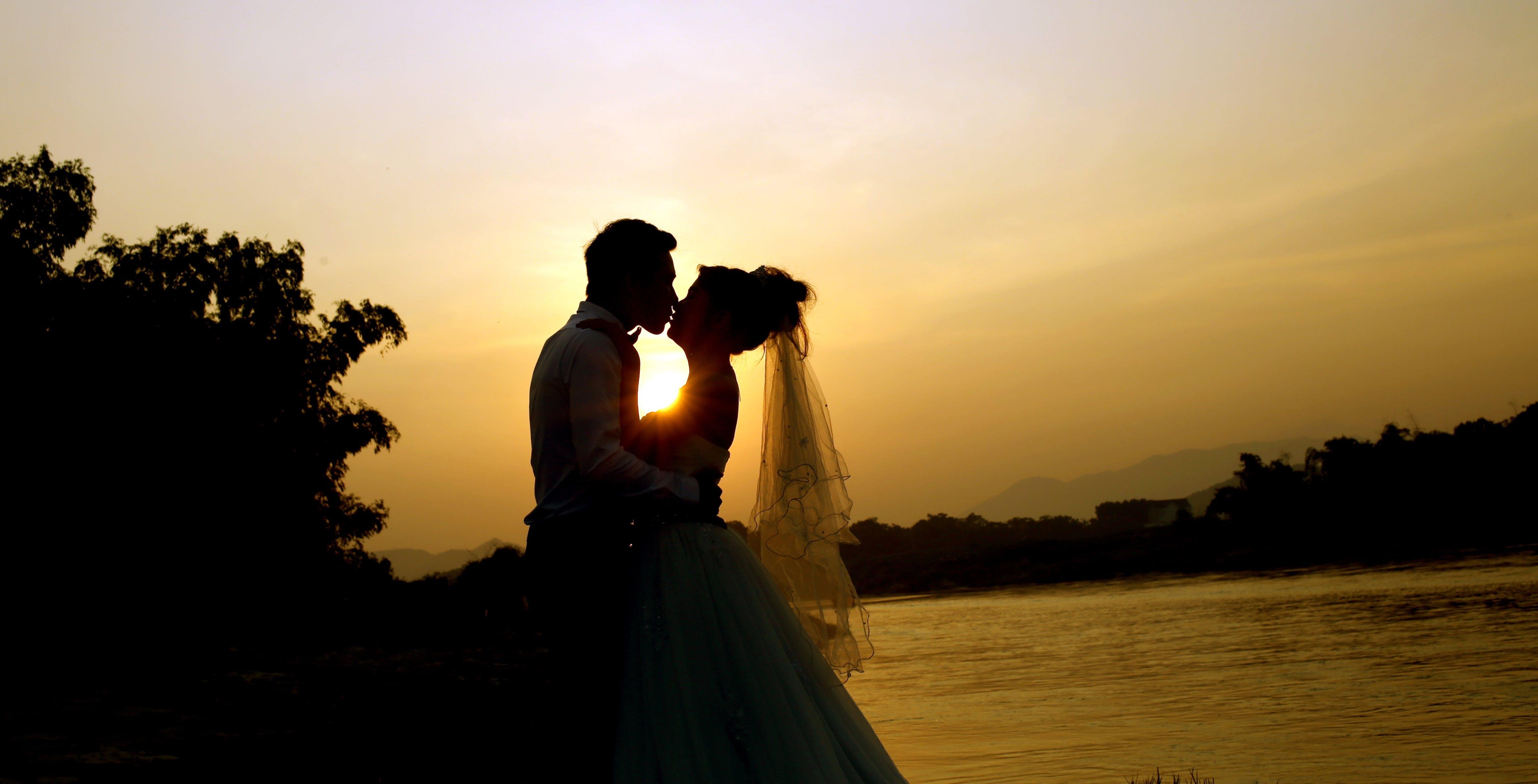 Man Kissing Woman Near Body of Water