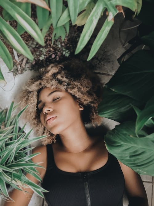 Woman sleeping on floor among pot plants