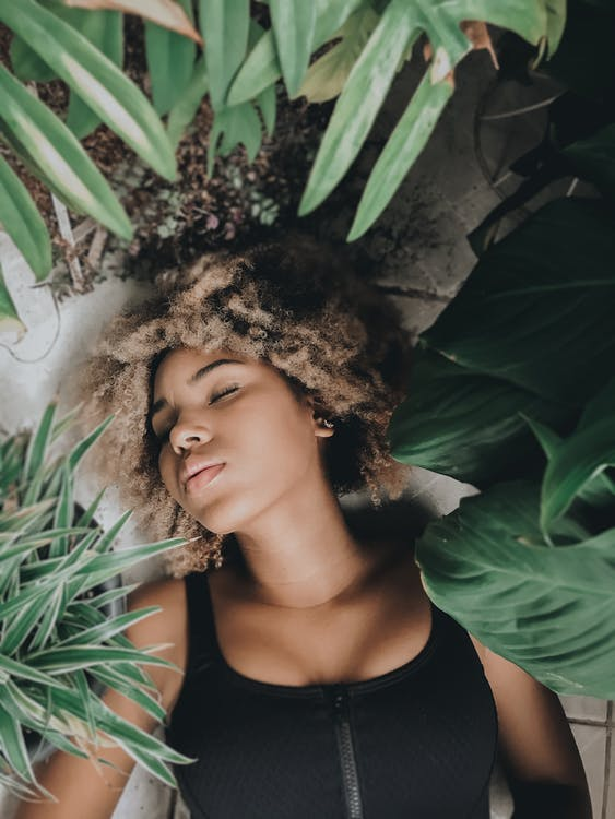 Overhead of gentle black woman with blond Afro hair resting on floor with eyes closed surrounded by pot flowers