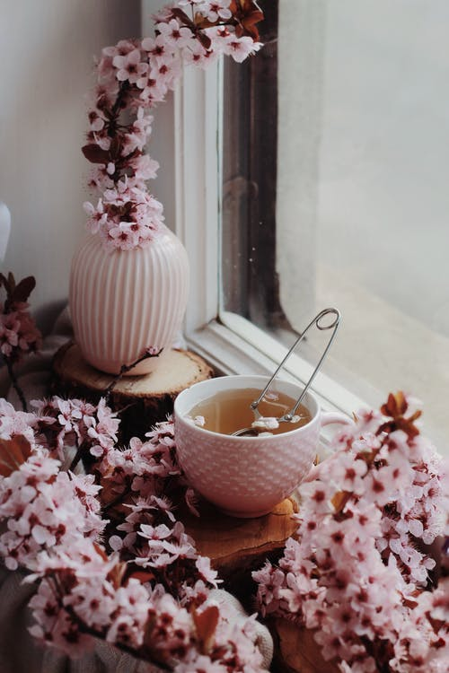 Metallic tea infuser in small white cup surrounded by tiny light pink delicate flowers by window in daylight