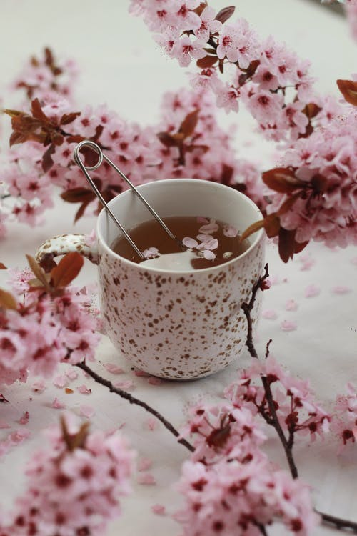 Spoon tea infuser in cup cup among flowers