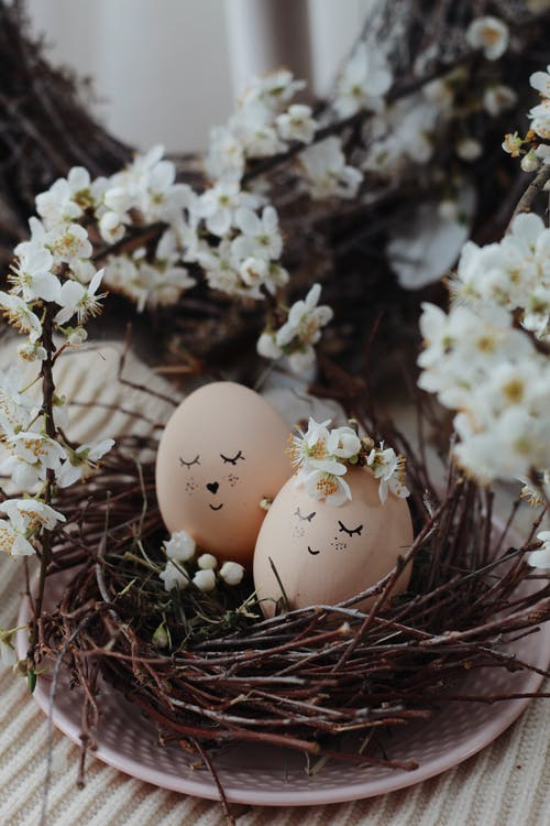 Fresh eggs with smiling faces in nest placed on table with flowers for Easter celebration