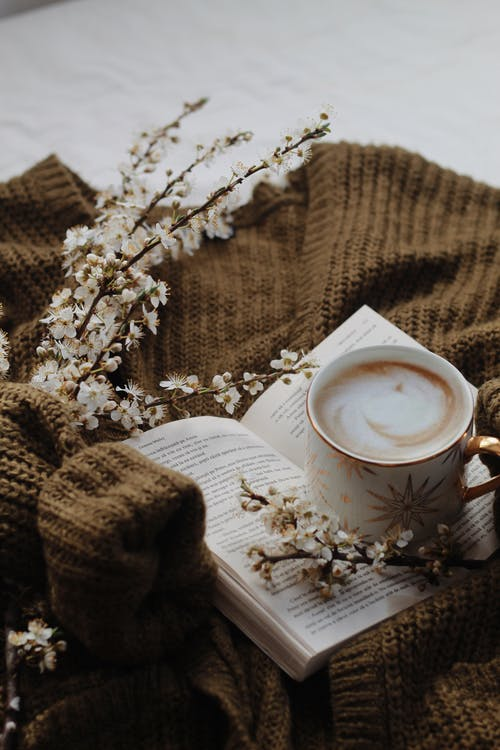 Cup of coffee and book on bed
