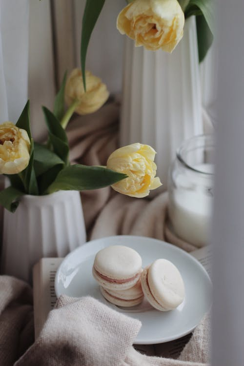 Set of sweet macaroons on plate placed in cozy room with blooming tulip flowers