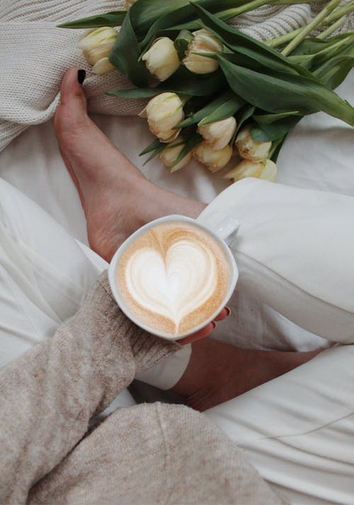 Crop woman with cup of coffee on bed