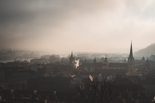 Amazing cityscape of medieval city with ornamental roofs and buildings on foggy day