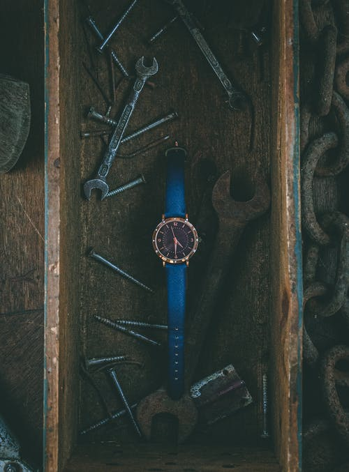 Tools and wristwatch placed in wooden box
