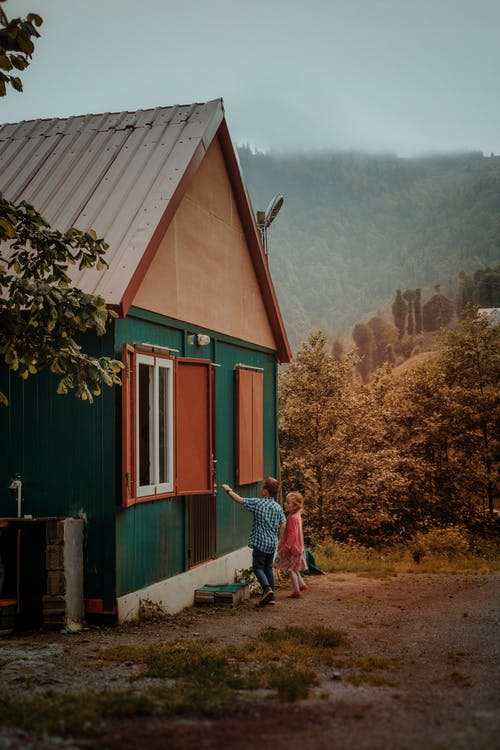 Anonymous little girl and boy standing near small house in countryside in gloomy weather