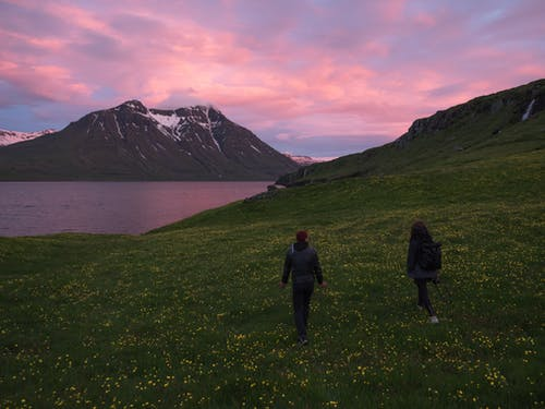 Couple walking on grassy hill near fjord in evening