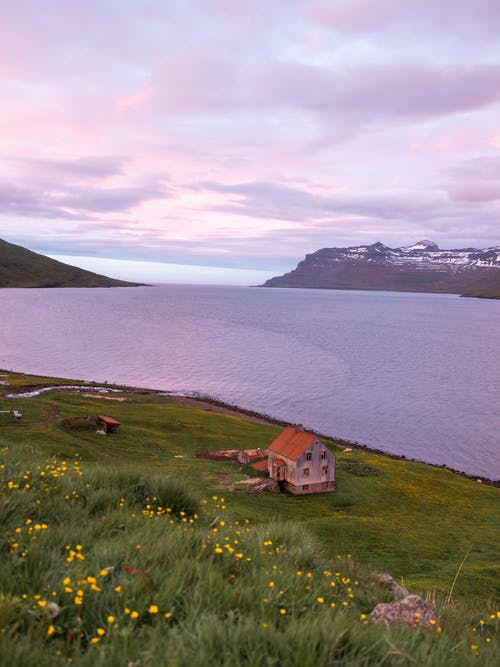Small house on grassy hill near fjord