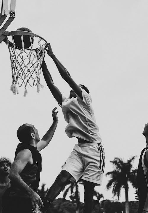 Unrecognizable black sportsman throwing ball into basketball net near friends