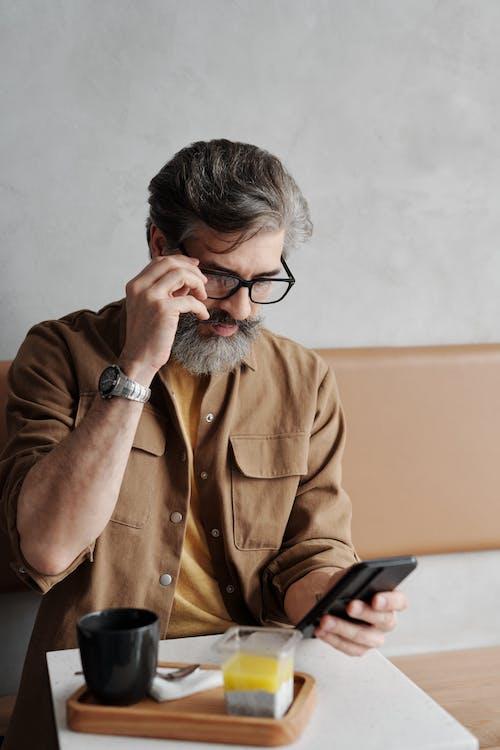 Man in Brown Button Up Shirt Wearing Black Framed Eyeglasses