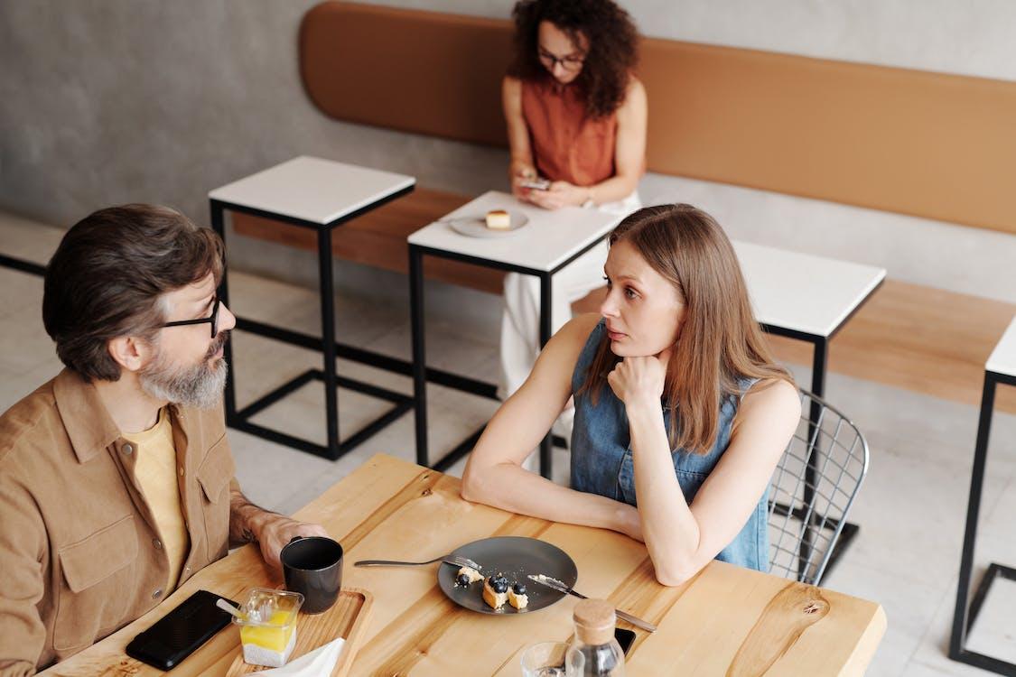 Woman in Blue Sleeveless Dress Sitting Beside Woman in Brown Cardigan