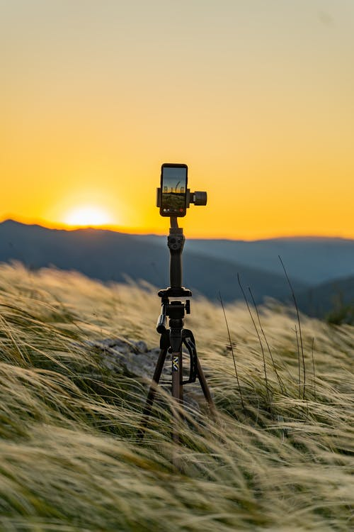 Modern tripod with mobile phone on grass hill behind ridge under colorful sky at sundown with shining sun in countryside