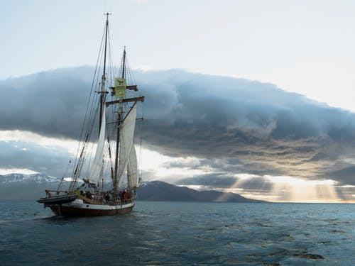 Beautiful ship sailing in sea during amazing sunset in cloudy day