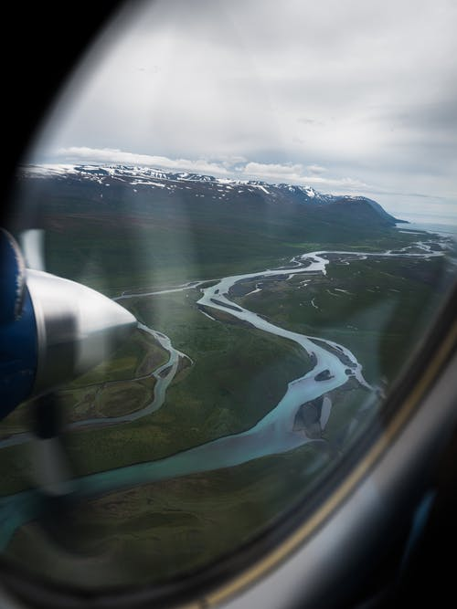 Through glass of picturesque view of curvy river flowing in mountainous valley near snowy hills