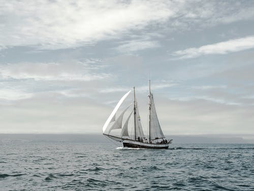 Lonely small ship sailing in sea against cloudy sky