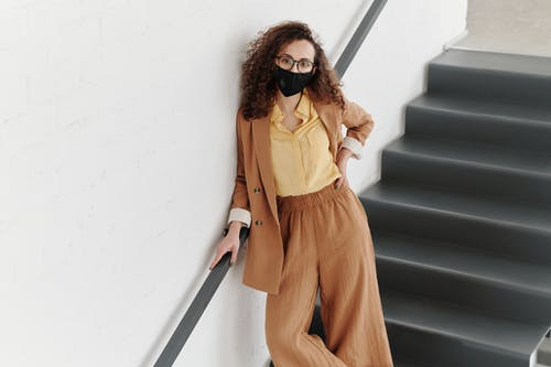 Woman With a Face Mask Standing on Stairs