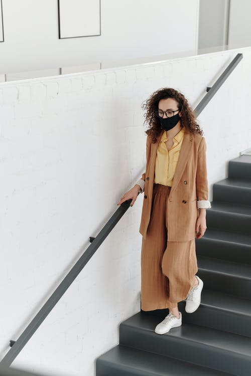 Woman Wearing a Face Mask Walking Down Stairs