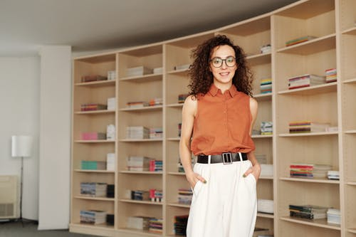 Woman in Red Tank Top and White Pants Standing Beside Brown Wooden Shelf
