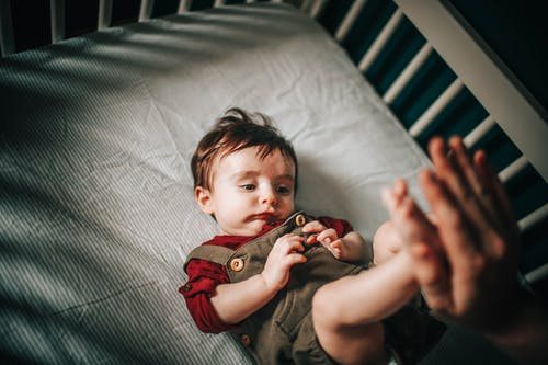 Unrecognizable parent playing with charming child in cot