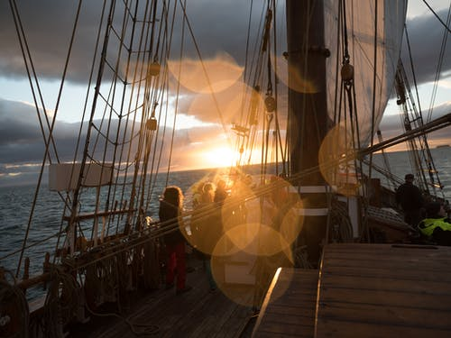 Wooden ship with unrecognizable passengers against sunset sky