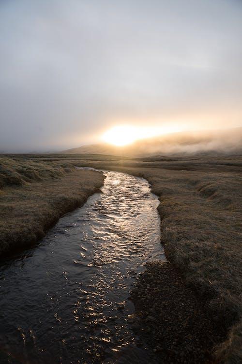 Lonely river in mountainous terrain during sundown