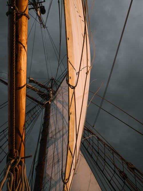White sail of boat against cloudy sky