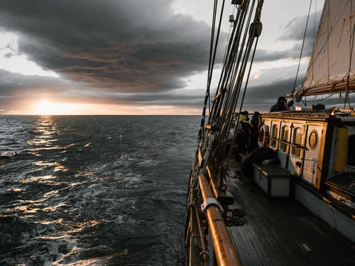 View of beautiful sunset over wavy ocean and dramatic sky from deck of wooden ship
