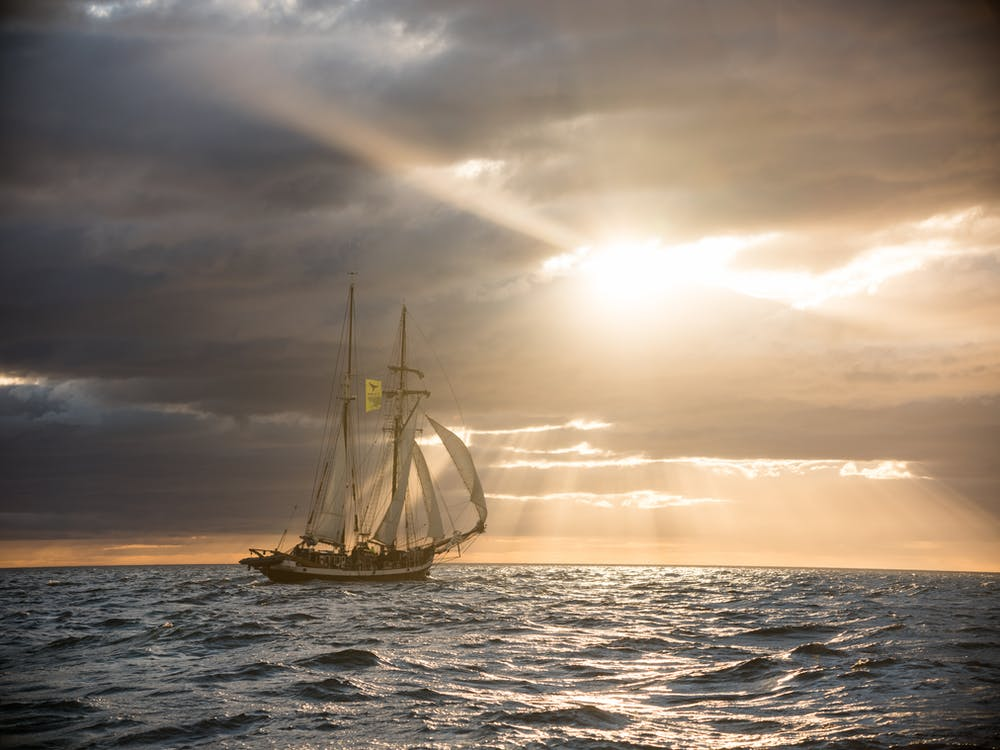 Ship sailing in ocean against cloudy sunset sky