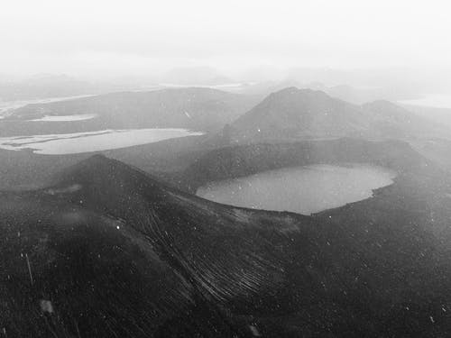 Volcanic terrain with mountains and geothermal lake in fog